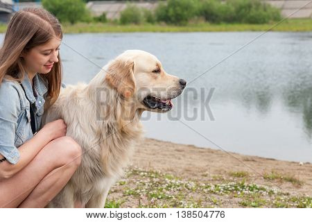 Portrait of a young girl and her dog golden retriever outdoors. Happy owner hugging her dog on the background of the lake in the summer.