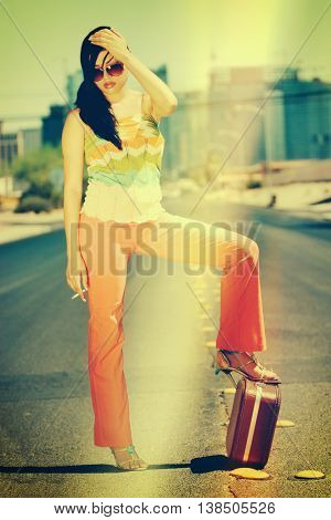 Beautiful smoking hitchhiking woman with suitcase