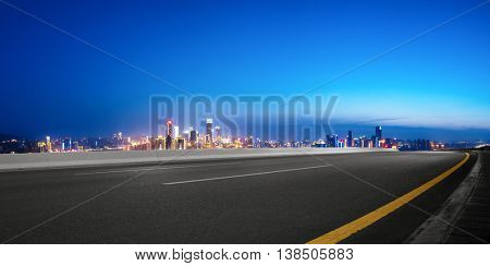 empty road with cityscape and skyline of chongqing at twilight