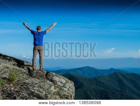 Feel the Mountain Fresh as a man stretches his arms out while looking out over a valley