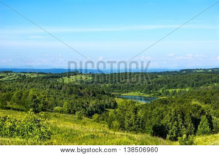 Summer beautiful hills landscape with blue lake. Scenic hillside landscape. Rolling hills and sky. Beautiful landscape.