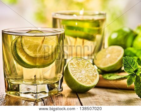 Country drink. On wooden boards are two short glasses with green transparent drink and half green lime . A drink number hundred fifty three mojito with mint leaf . Country life. Light background.