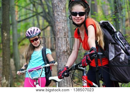 Bikes cycling family. Happy mother and daughter wearing helmet are cycling on bicycles into summer park.