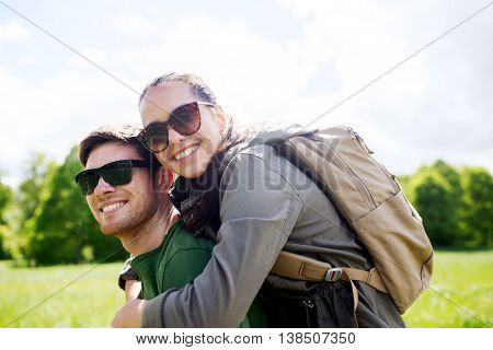 travel, hiking, backpacking, tourism and people concept - happy couple in sunglasses with backpacks having fun outdoors
