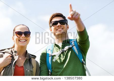 travel, hiking, backpacking, tourism and people concept - happy couple with backpacks outdoors pointing finger to something over sky