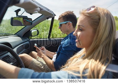 leisure, road trip, travel and people concept - man texting on smartphone driving in cabriolet car with his girlfriend