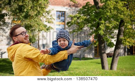 family, childhood, fatherhood, leisure and people concept - happy father and little son playing and having fun outdoors over summer city yard background