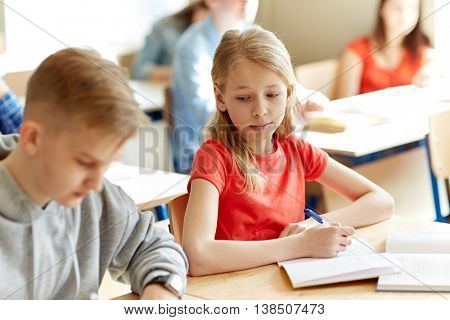 education, learning and people concept - group of students with books writing school test and girl cheating