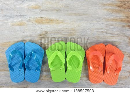 Row of colorful summer flip-flops on weathered wood.
