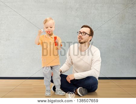 family, childhood, fatherhood, leisure and people concept - happy father and little son blowing bubbles and having fun over home room background