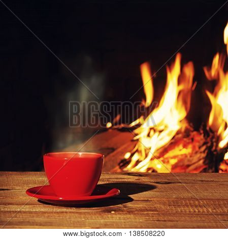 Red Cup Of Tea Or Coffee Near Fireplace On Wooden Table.