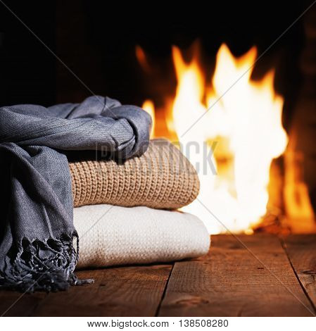 Warm Woolen Things Near Fireplace On Wooden Table.