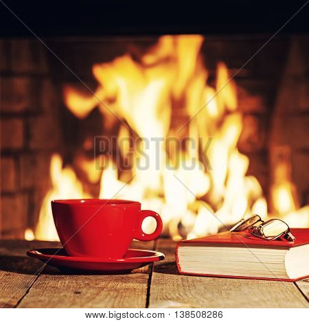 Red Cup, Glasses And Old Book Near Fireplace On Wooden Table.