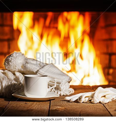 White Cup Of Coffee Or Tea, Woolen Scarf, Gloves And Cap On Wooden Table Near  Fireplace.