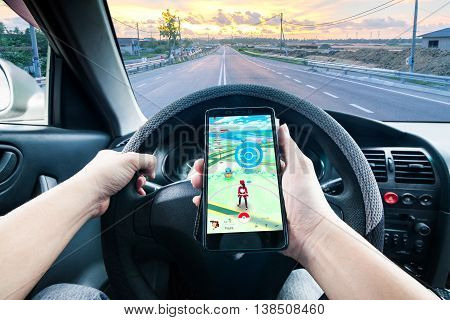 California, United State, 15 July 2016 : Pokémon Go is a free-to-play location based augmented reality mobile game developed by Niantic and published by The Pokémon Company as part of the Pokémon franchise.  A man driving while playing Pokemon Go indicati