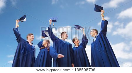 education, graduation and people concept - group of smiling students in gowns waving mortarboards over blue sky and clouds background