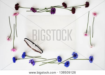Glasses And Paper With Wreath Frame From Wildflowers.