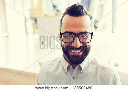 business, startup, and people concept - happy smiling latin man with eyeglasses and beard at office