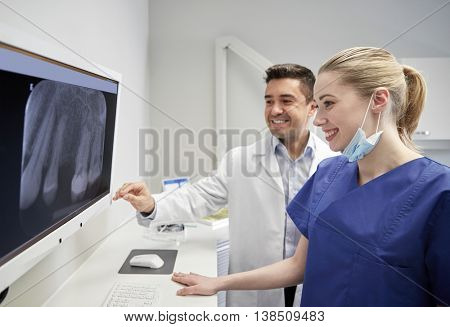 people, medicine, stomatology, technology and health care concept - happy dentists looking to x-ray scan on monitor at dental clinic