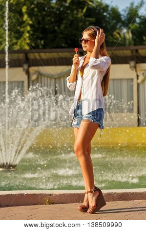 Girl enjoying music with headphones. The girl in sunglasses and a white shirt. She licks a lollipop. The girl is very long legs