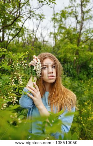 Young attractive girl holding flowers acacia. Hippie girl. Unity with nature.