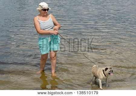 Aged Woman With Pet Are Standing On River Water Edge.