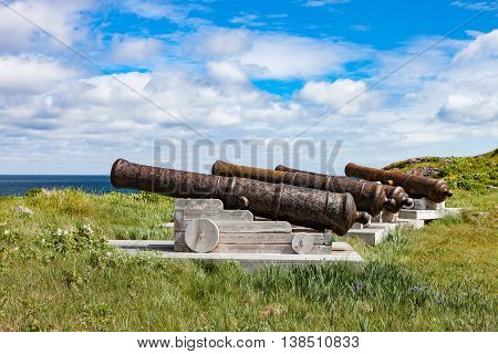 A set of ancient cannons against a blue summer sky