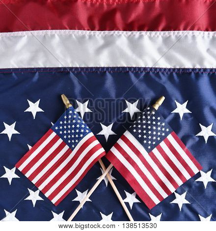 Two small American Flags on a larger Flag. Top view in square format.