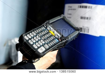 Hand of a person using a bar scanner to read information on a retail product while checking price or inventory in a shop