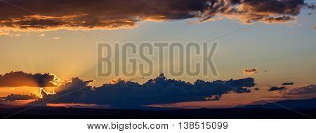 Majestic vivid sunset/sunrise with dark heavy clouds and sunrays