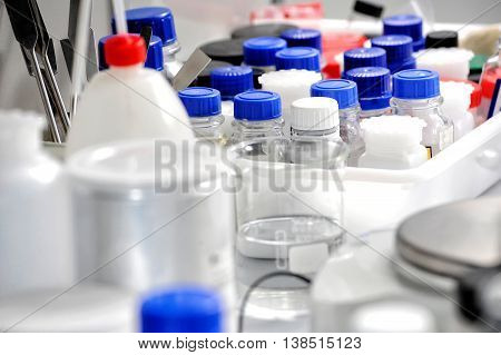 Close up on various bottles and in white and blue along with clear glass beaker in box