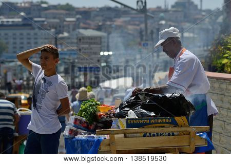 ISTANBUL - AUGUST 8: Unknown man trades traditional turkish food in a street near harbor, August 8, 2013 in Istanbul, Turkey. Istanbul is the world's fifth-most-popular tourist destination.