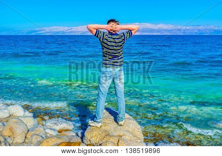 The man on the shore of the Dead Sea enjoy being in Earth's lowest elevation on land Ein Gedi Israel.