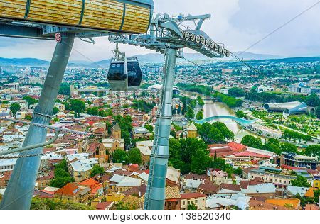 The view on the red city roofs with the constructions of the cableway located on Sololaki Hill Tbilisi Georgia.