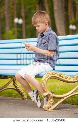 Boy sitting on a bench , listening to music and looking at the phone