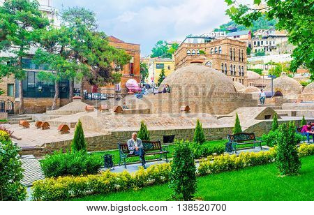 TBILISI GEORGIA - MAY 28 2016: The brick domes of the old sulphur baths in Abanotubani neighborhood surrounded by green garden with comfortable benches on May 28 in Tbilisi.