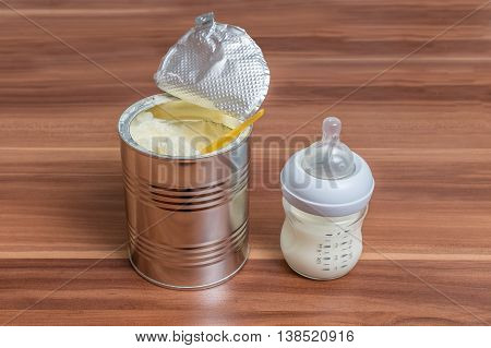 Powdered Milk Formula In Can And Bottle For Feeding Baby On Wood
