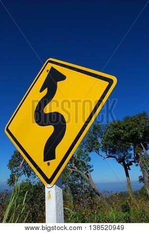 a winding road traffic sign with blue sky