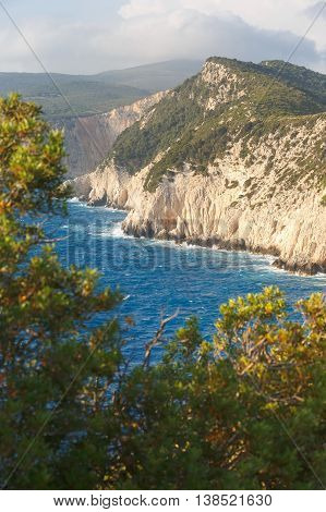 Lefkada island, west coast cliffs and blue sea water waving at coast. View from lighthouse, Cape Ducato