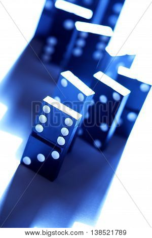 Black dominoes standing in a row on white background