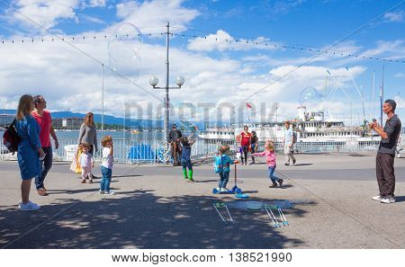 GENEVA SWITZERLAND - JUNE 17 2016: The children and with soap bubbles attraction at Lake promenade in the old town of Geneva Switzerland on 28 July 2010. It is the second most populous city in Switzerland.