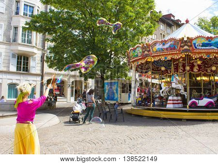 Geneva Switzerland - June 17 2016: The children and with soap bubbles attraction near the city carousel in the old town of Geneva Switzerland on 28 July 2010. It is the second most populous city in Switzerland.