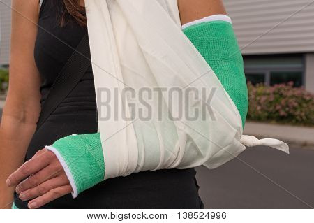 Woman with broken arm in a supporting strap