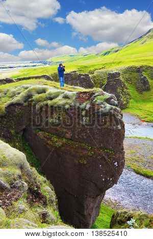 Fantastic country Iceland. The enthusiastic tourist on a rock canyon  Fjadrargljufur