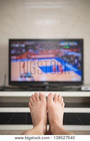 man laying down on a sofa at home watching basket match on tv