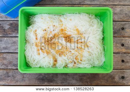 white rice noodles in green box on wood table