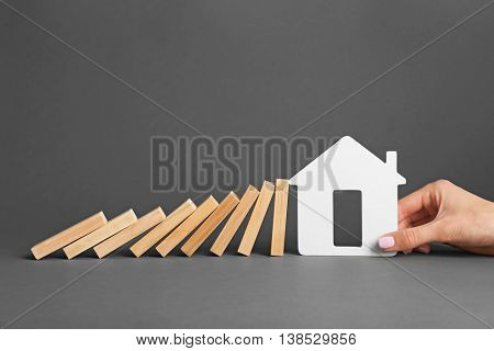 Female hand holding house shape with falling row of dominoes