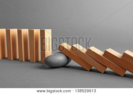 Stone blocked row of falling dominoes on grey background