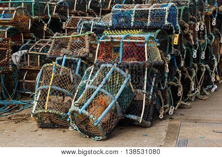 Lobster pots stacked on the quayside. In Staithes North Yorkshire England.