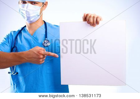 surgeon in the mask holds a placard.